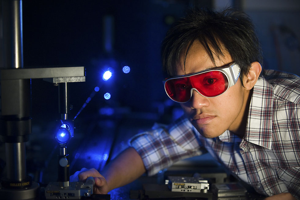 Engineering student working with a laser